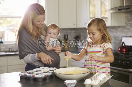 young girl preparing cake mix in
