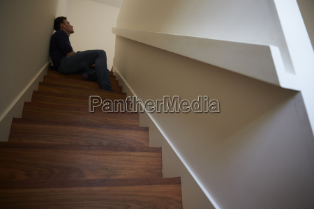 depressed young man sitting on stairs