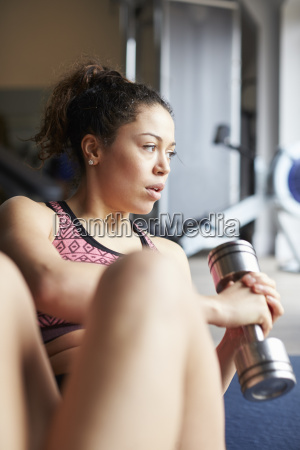young woman exercising with weight in
