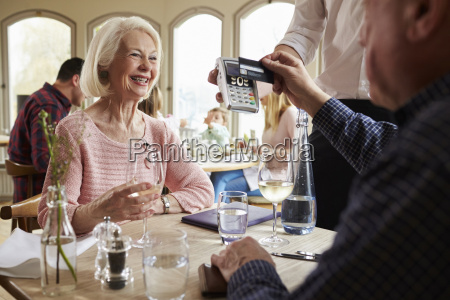 senior couple with waiter paying bill