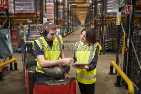female warehouse manager instructing man on
