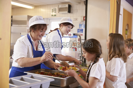 two women serving food to a