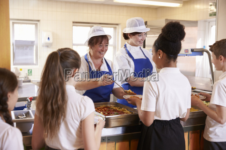two women serving kids food in