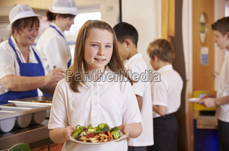 girl holds a plate of food