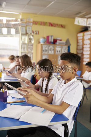 kids use tablet computers in primary