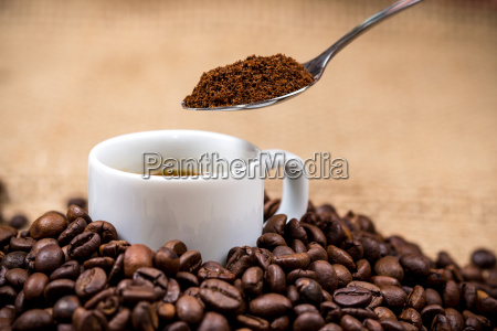 white coffeecup on coffeebeans with spoon