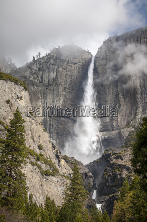 a waterfall with fog in a