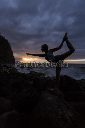 yoga woman balances on a rock