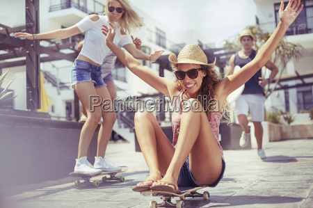 playful young woman riding skateboard