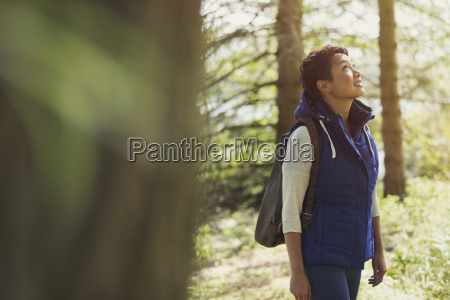 woman hiking with backpack looking up
