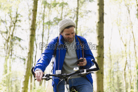 man mountain biking texting with cell