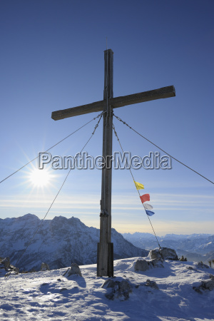 cross and buddhist prayer flags at