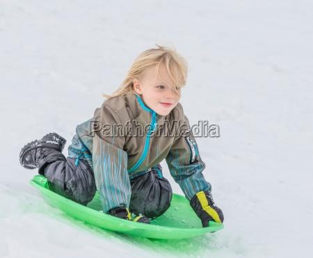 boy playing on toboggan in snow