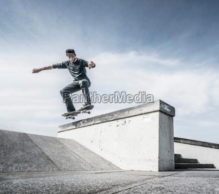 junger mann skateboarden auf dem dach