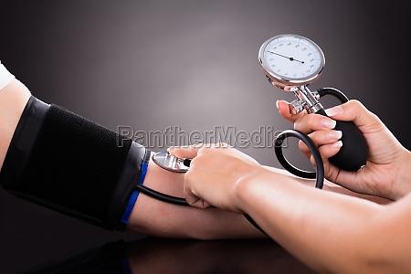 doktor der blutdruck des patienten ueberprueft