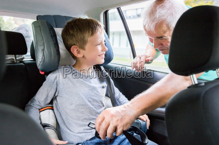 grandfather buckling up on grandson in