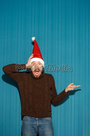 ueberrascht weihnachtsmann der einen sankt hut