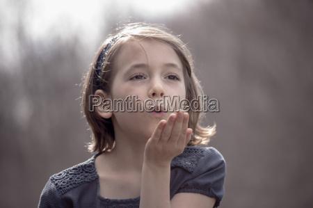 portraet des huebschen maedchens blaest einen