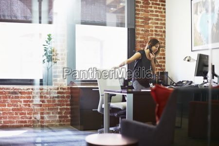 young woman using telephone in office