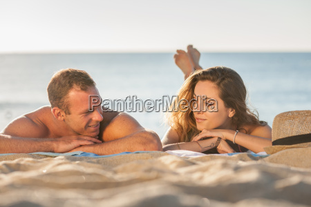romantic young couple sunbathing on beach