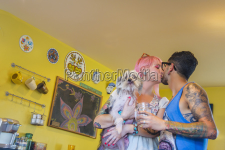 couple kissing in kitchen whilst carrying
