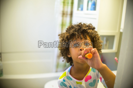 portrait of girl brushing teeth in