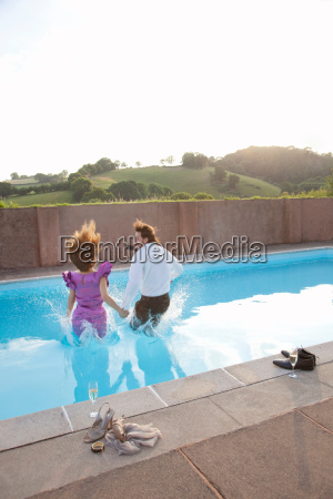 couple jumping into pool dressed