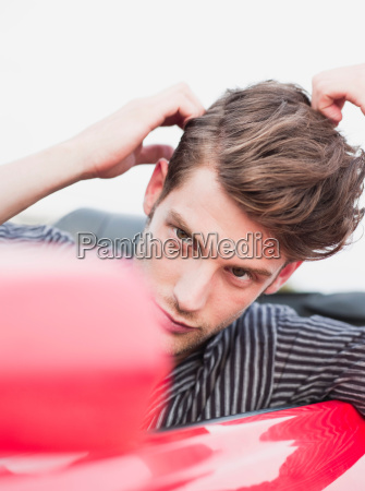 man looking into side mirror of