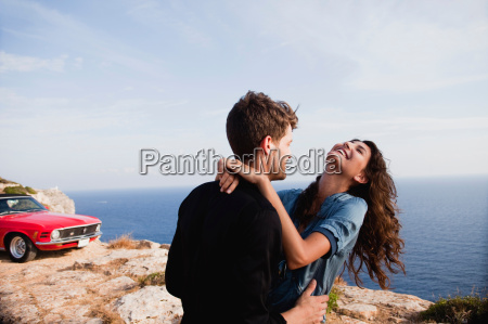 couple standing at cliff in front
