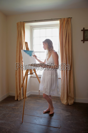 young woman painting by window