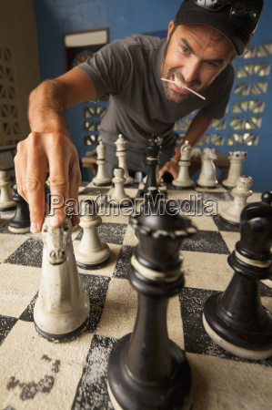 mid adult man moving chess piece
