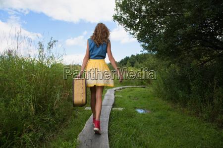 teenage girl carrying suitcase on rural