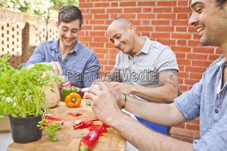 three male friends laughing and preparing