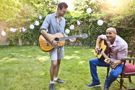 two male friends playing acoustic guitar