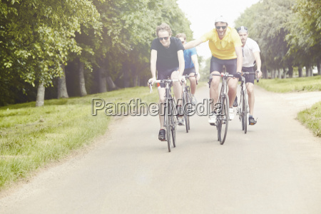 cyclists riding on leafy countryside road