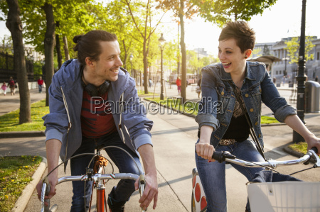 young adult couple cycling through city