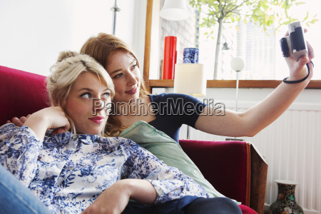 young women sitting on sofa taking