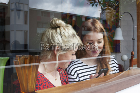 young women through window looking at