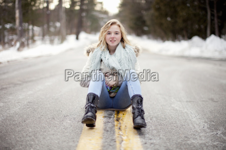 young woman sitting on road through