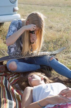 young woman photographing friend lying on