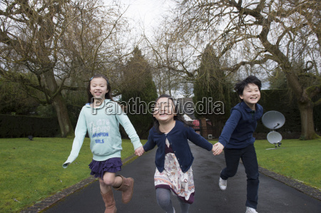 young friends running through park holding