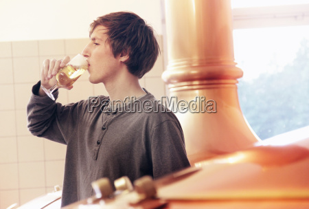 young man tasting beer in brewery