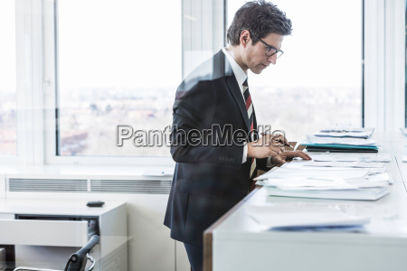 businessman standing in office looking at