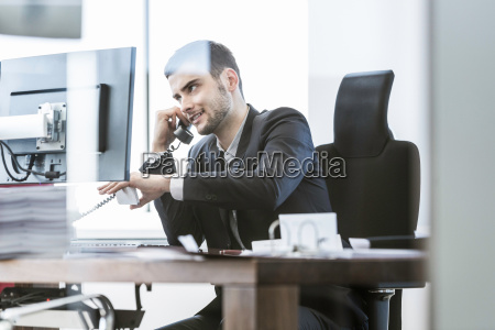 businessman sitting at desk with computer