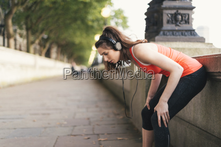 young female runner wearing headphones taking