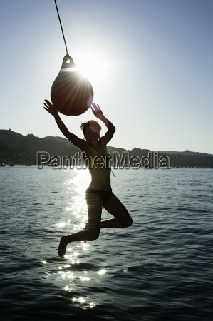 young woman swinging from boat fender