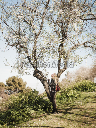 female tourist looking up at tree