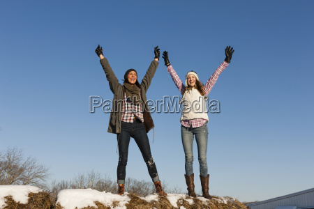 two young women with arms raised