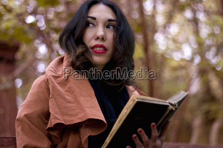 young woman in park reading book