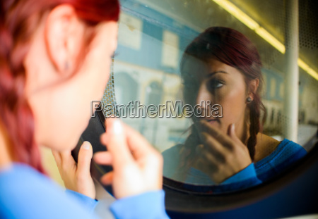 young woman in laundromat looking at